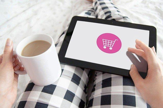 Frau mit Kaffee in der Hand und einem Padlett (Shop-Symbol)