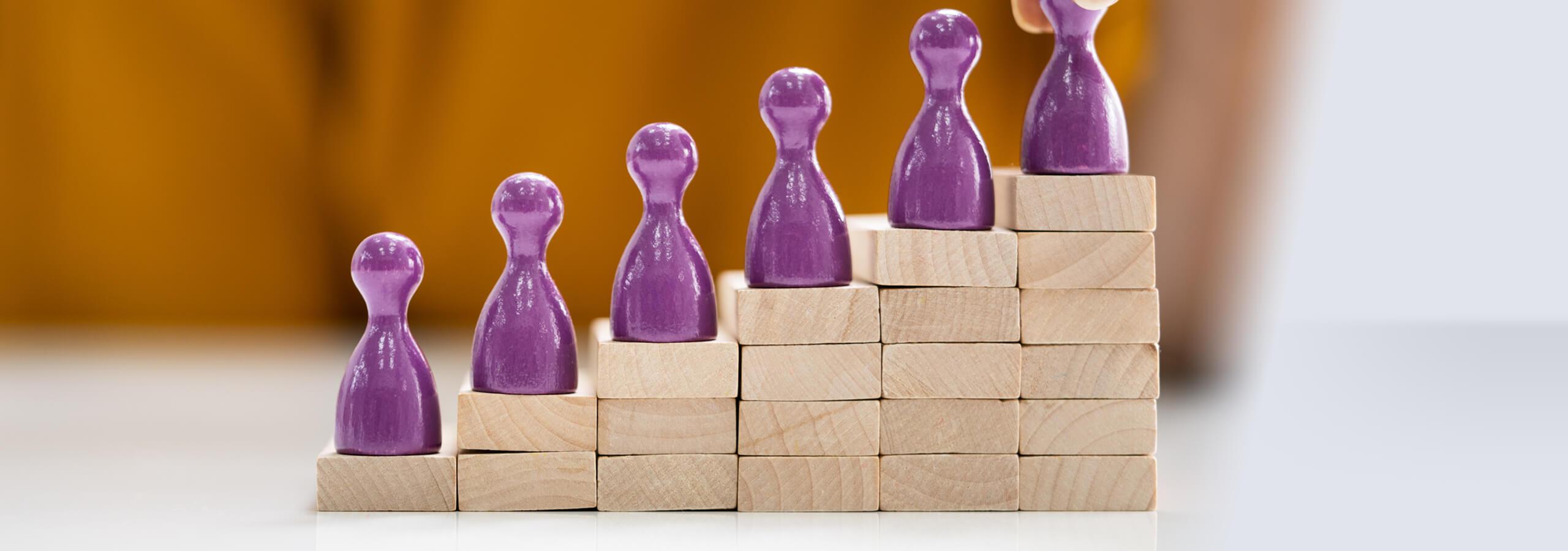 Symbolbild: Gleichstellung auf dem Arbeitsmarkt Holztreppe mit Spielfiguren auf jeder Stufe